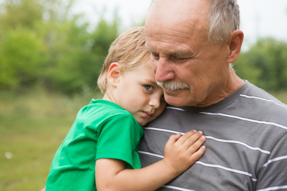 Aging grandfather carrying child who's hugging him