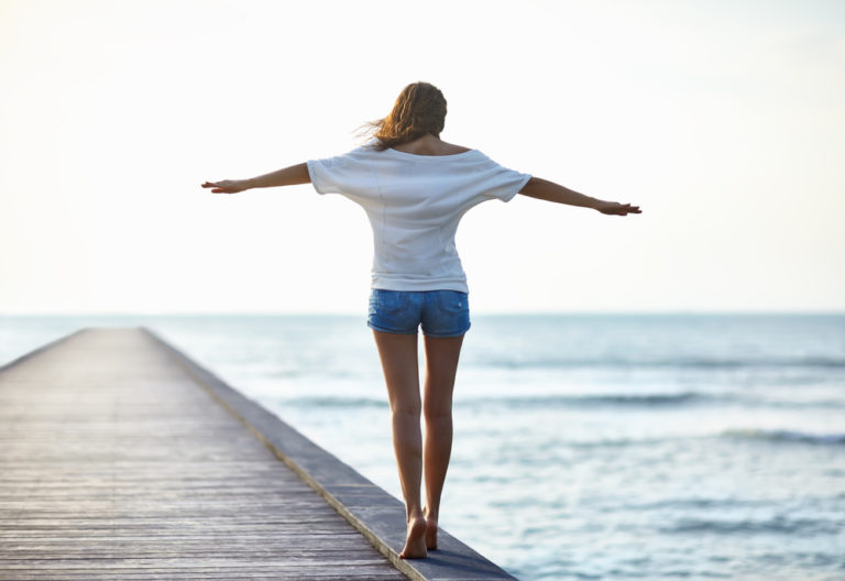 Woman with arms outstretched walks along edge of dock