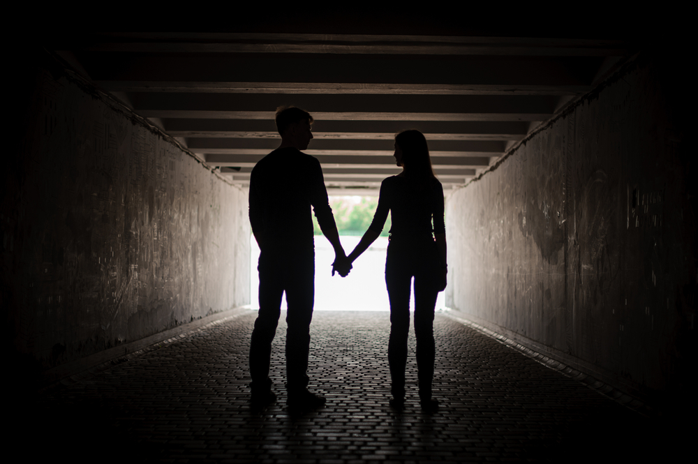 silhouette of man and woman holding hands in a tunnel