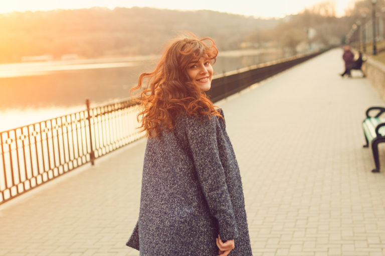 plus size woman smiling and walking at sunset