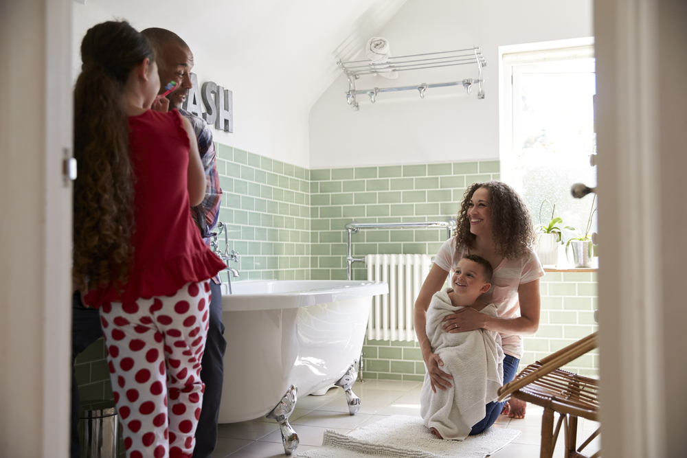 mother and father towel children off in bathroom at home