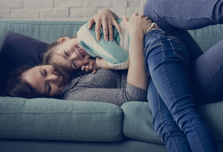 Mother and child laugh and play on couch together