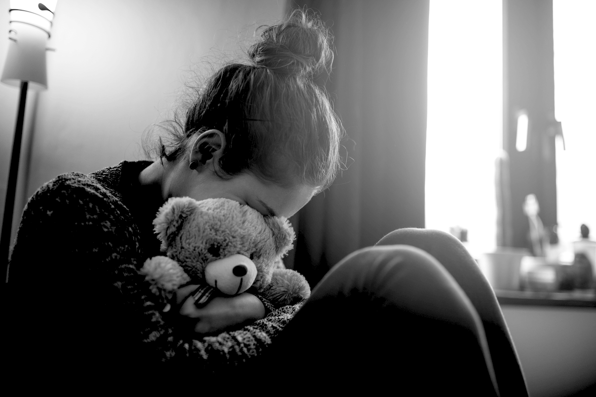 Grieving mother holding a teddy bear
