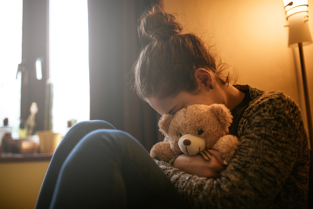 sad woman hides her face in teddy bear after miscarriage