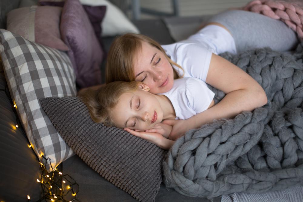 Mom hugs teenage daughter who is sleeping on her bed