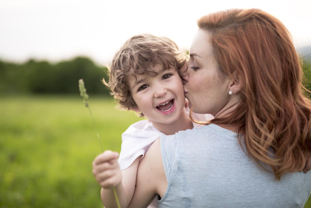 Mom kissing son on cheek in summer sun