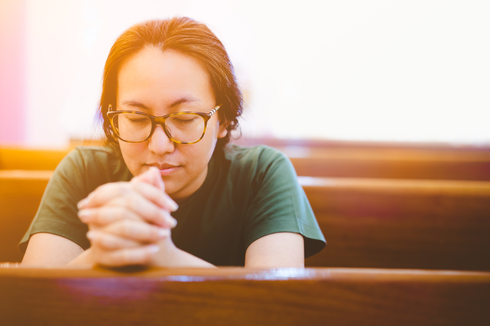 Woman in church pew praying with smile