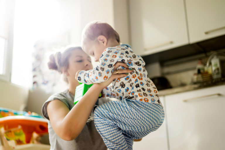 toddler boy playing with his mother in the kitchen at home