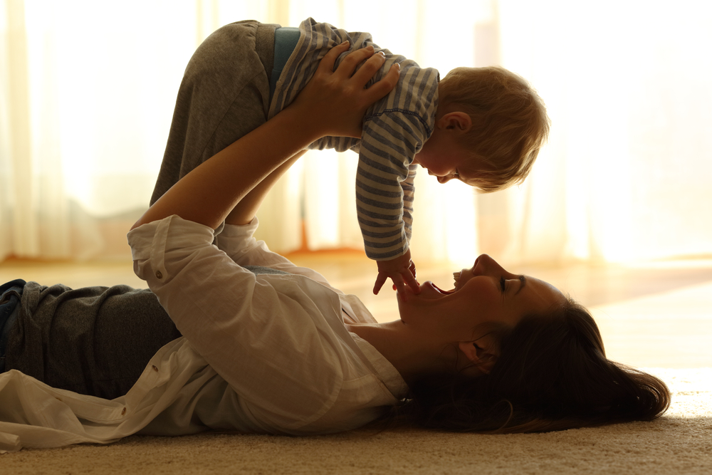 A happy mother lifts her child on the floor at home