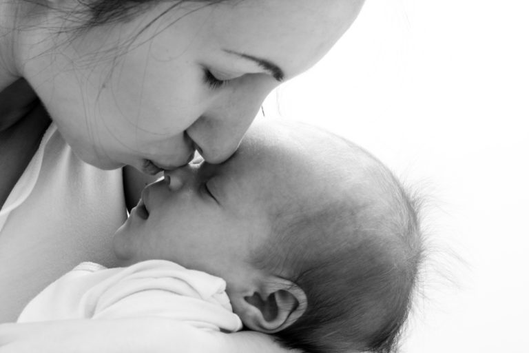 Mother kissing newborn daughter on the nose
