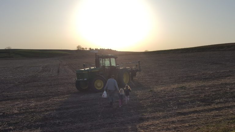 Farmer and his kids walking to tractor on the farm