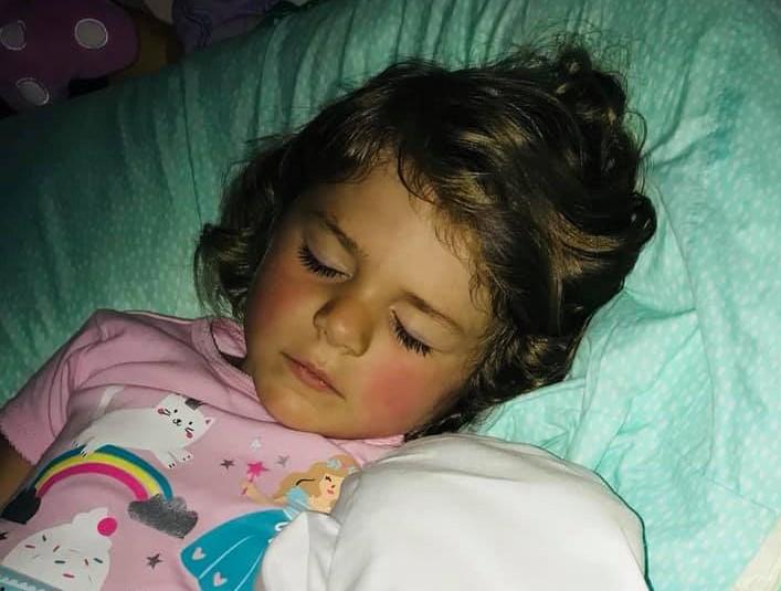 Sleeping little girl with pink pajamas