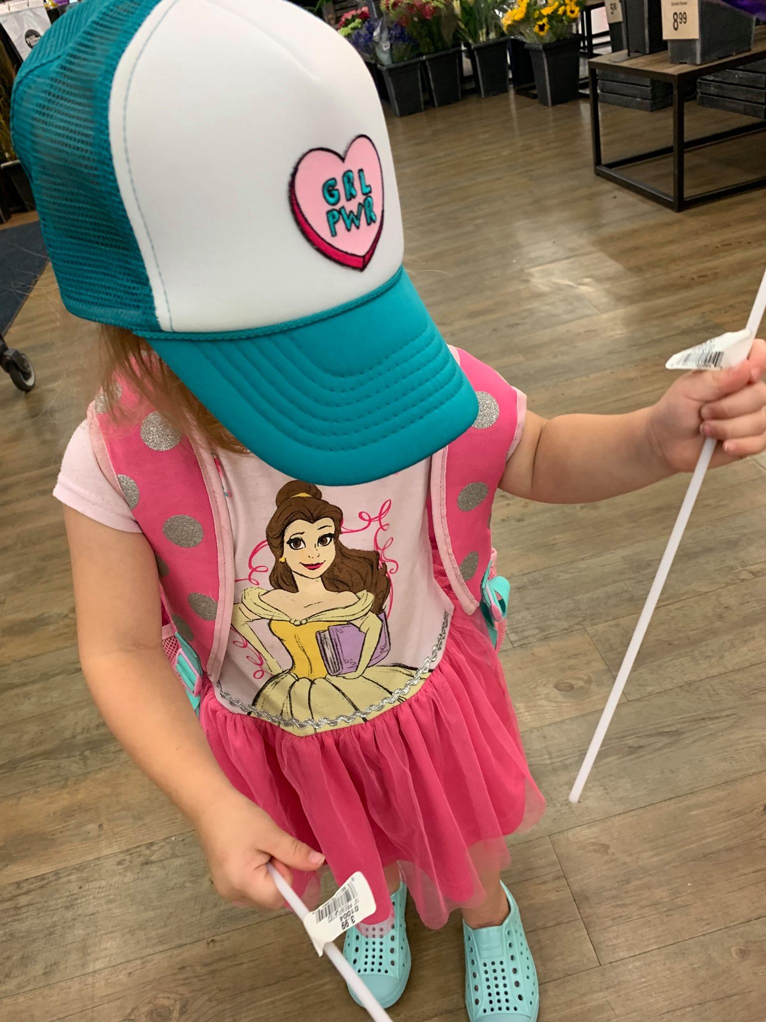 Toddler wearing a baseball cap and pink shirt