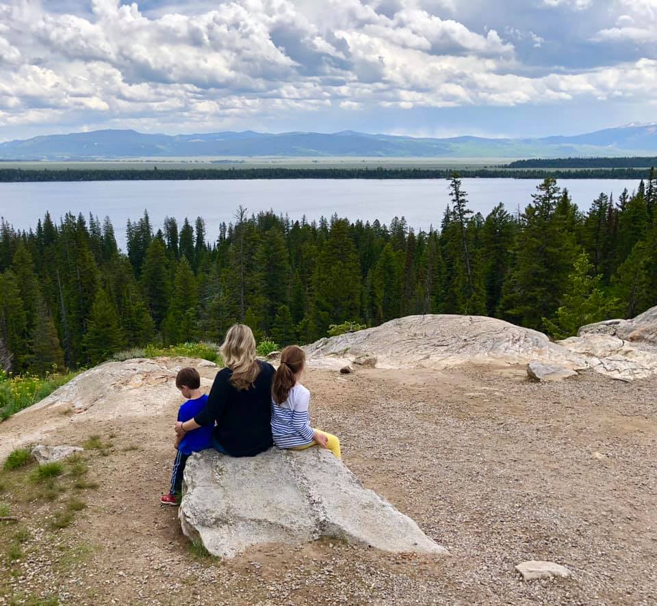 Mother sitting on a rock with two children looking at scenery