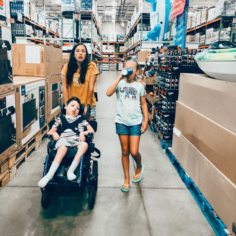 Siblings walk together in store pushing child in a wheelchair