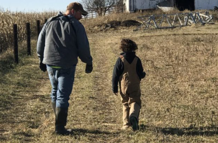 Farmer walking to a field with his young son in overalls