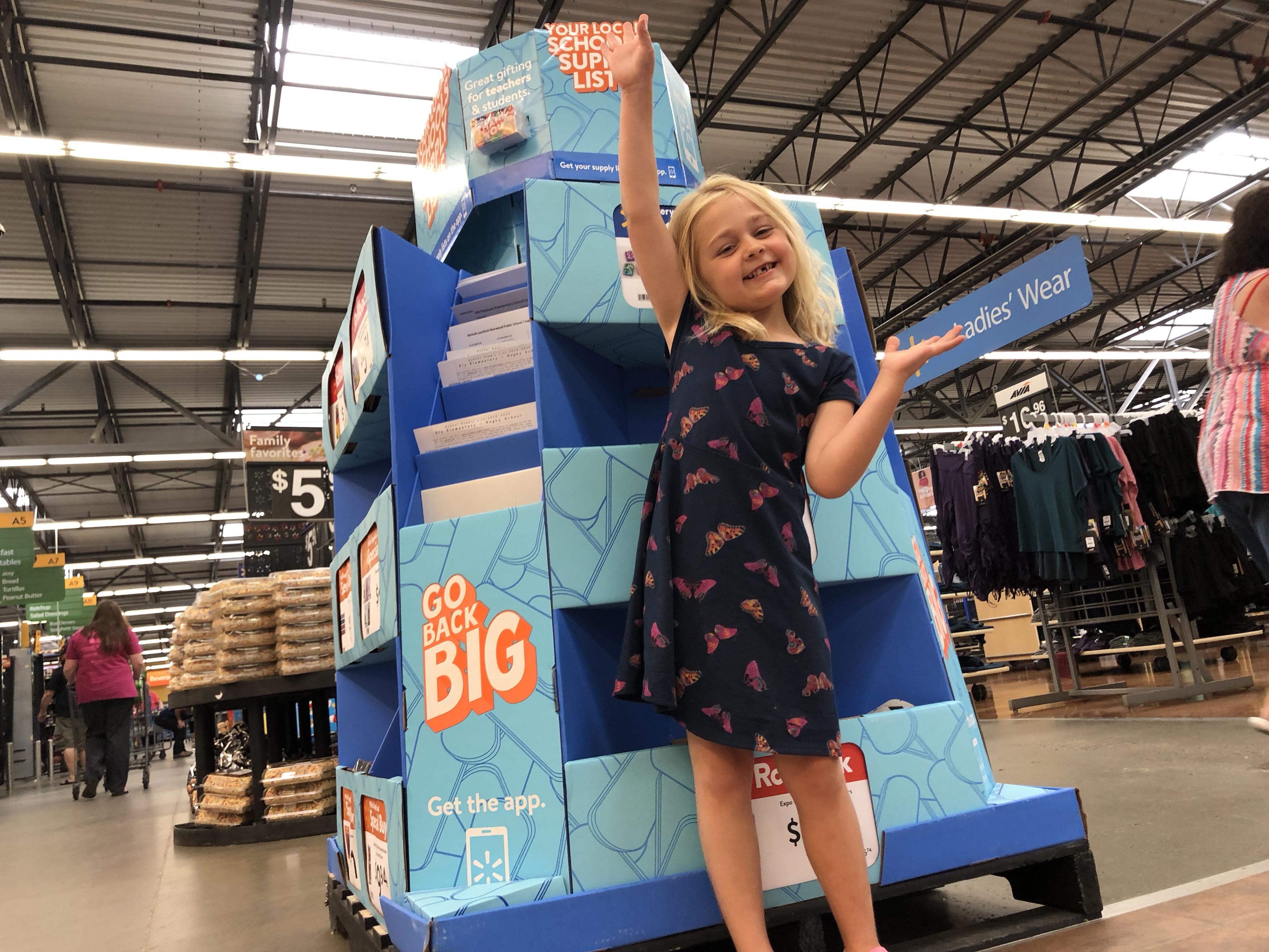 Kindergarten student stands in front of Go Back BIG sign at Walmart