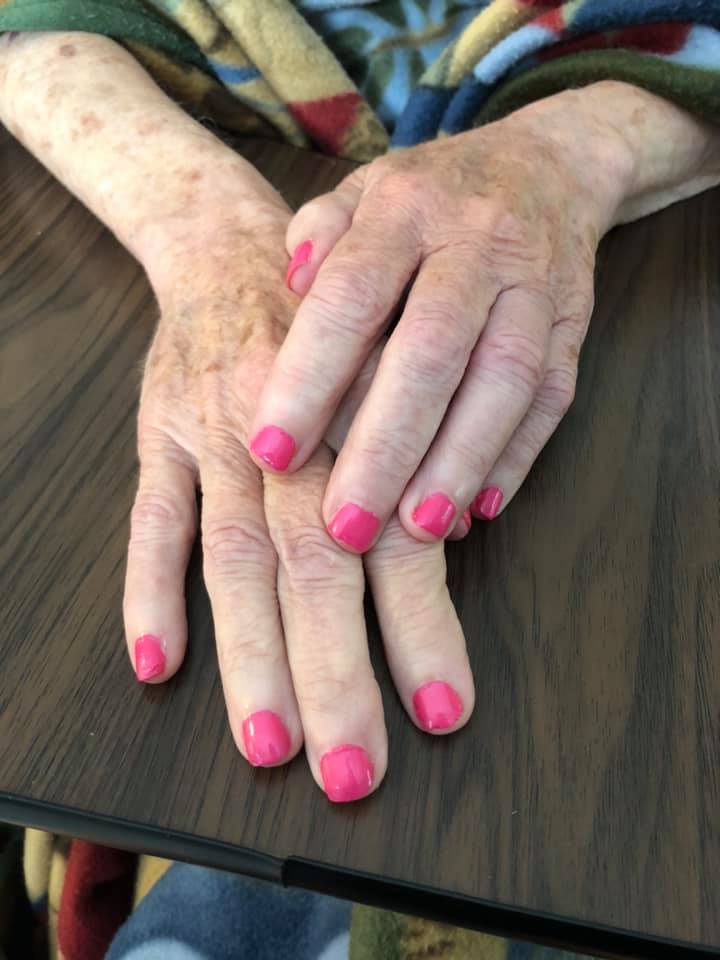 Elderly woman's hands resting on table