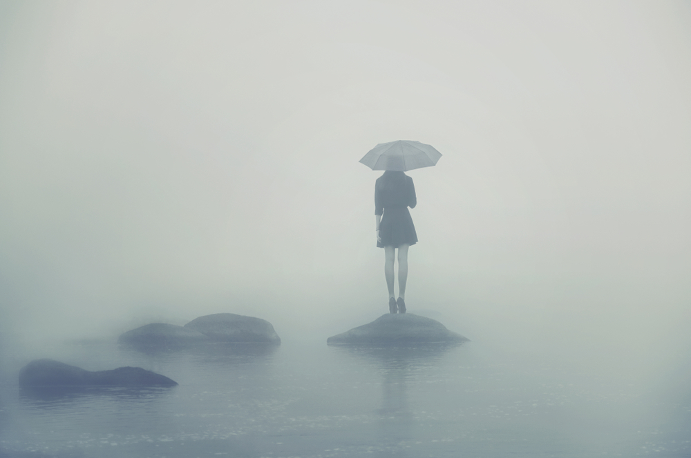 Sad woman stands on a rock in the fog with umbrella