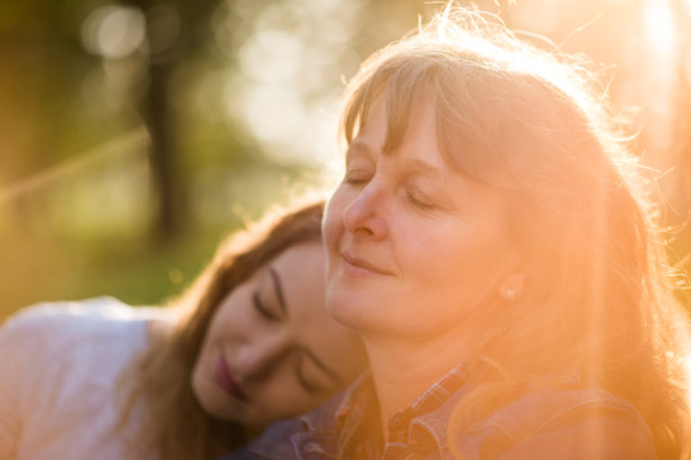 Grown daughter lays her head on her mother's shoulder