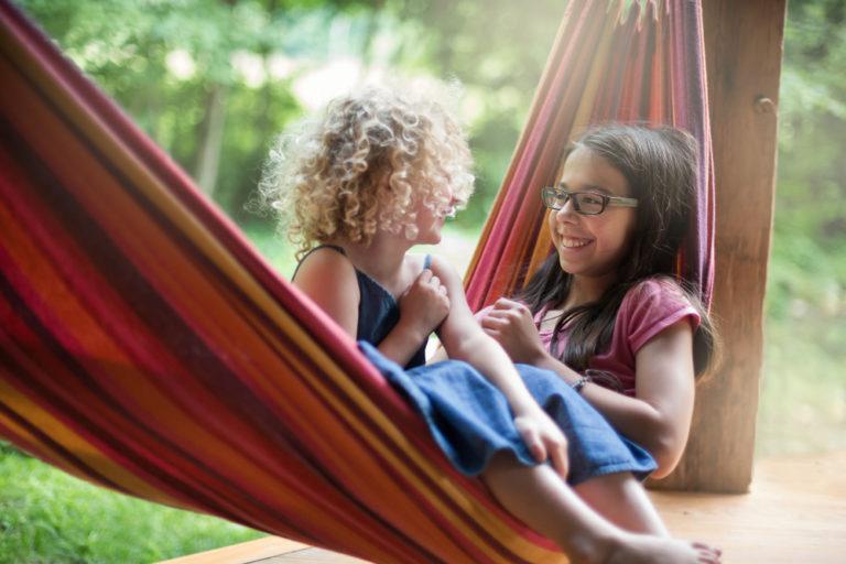 Two tween girls swinging on a hammock together