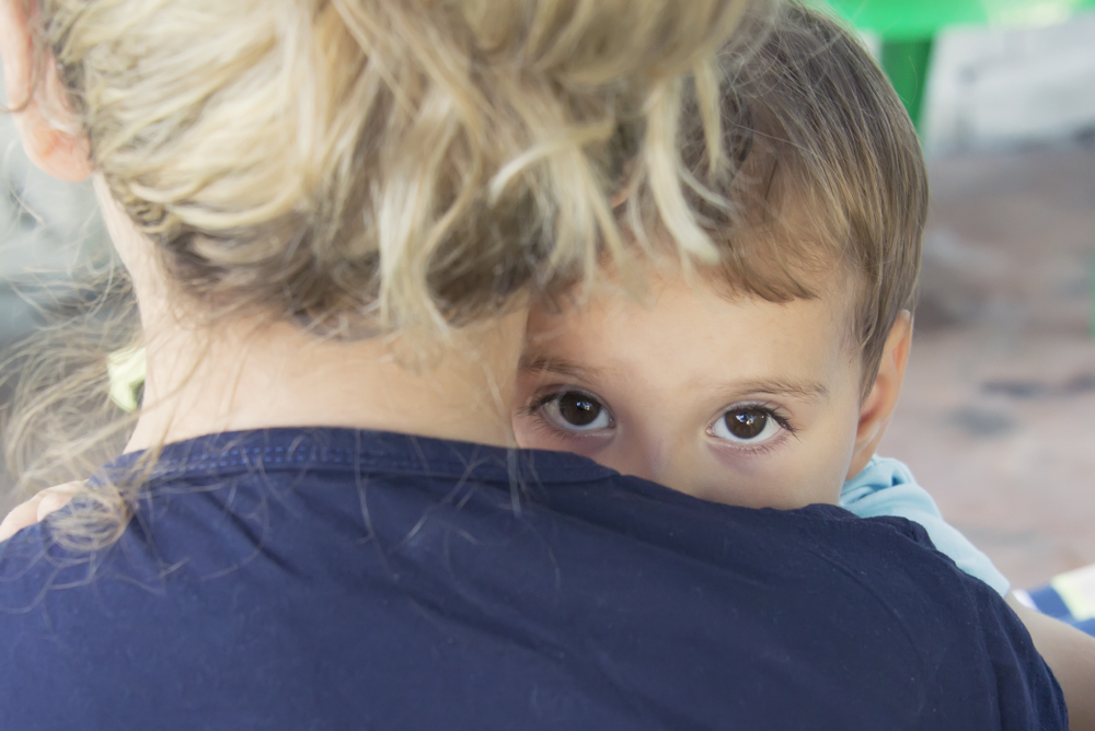 Little boy's eyes show over his mother's shoulder