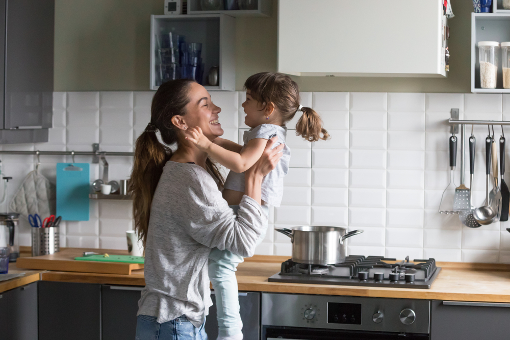 Mother and child in the kitchen laughing at home