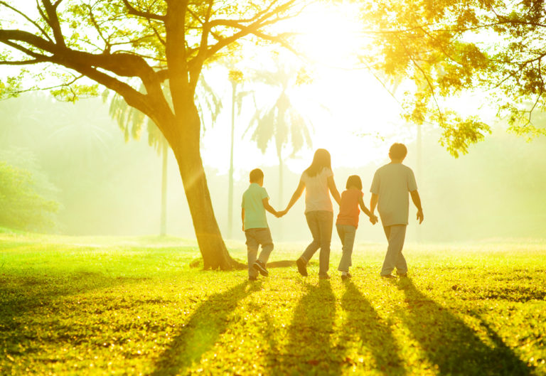 family of 4 walking holding hands in afternoon sunlight