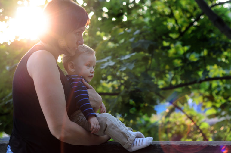 Mother holds her toddler son with sun flare in background