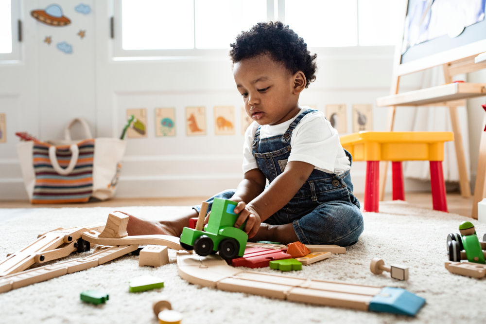 Toddler boy sitting on the floor playing with trains