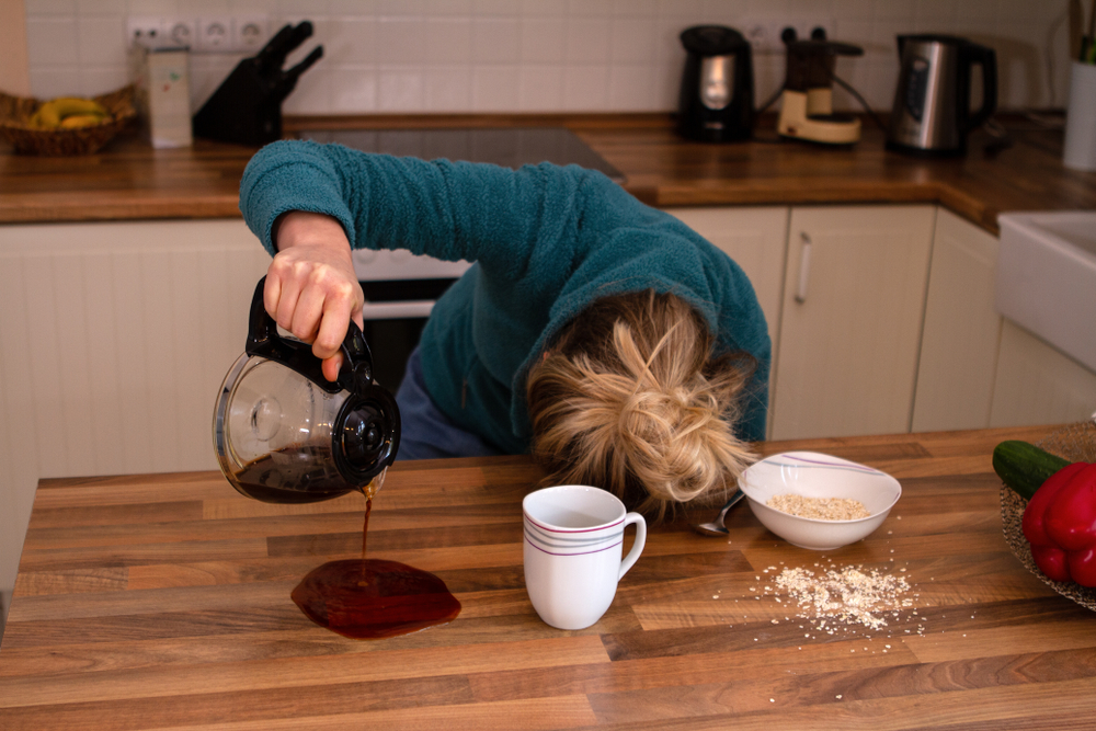 Tired woman spilling coffee with her head on table