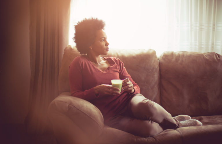 Woman sitting on couch at home alone in sunlight