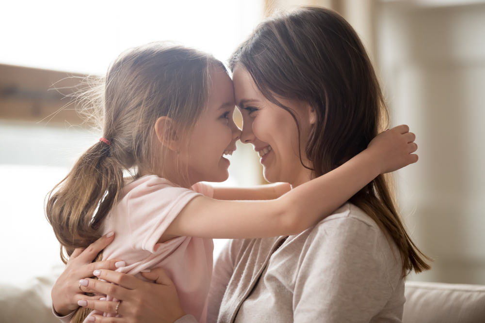 Mother and daughter touch foreheads and smile at each other