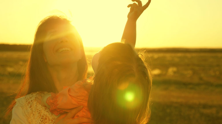 Mother and child look up at sunset in sun flare