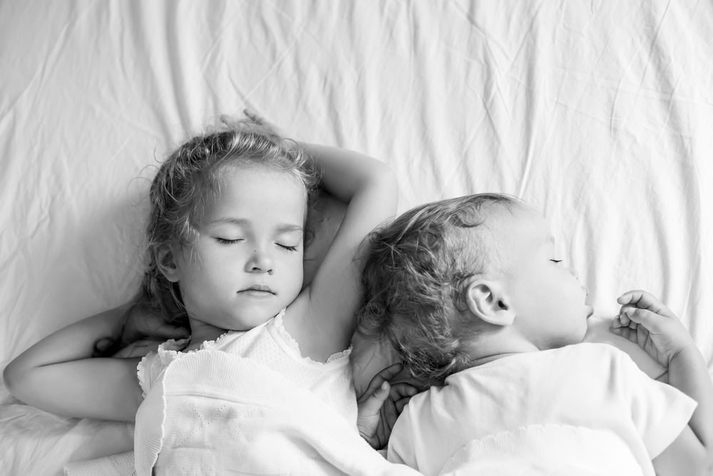 Two children sleeping in black and white photo