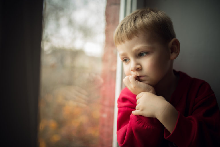 sad child looking out window
