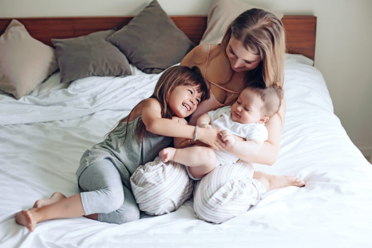 Young mother with toddler and new baby on a bed at home