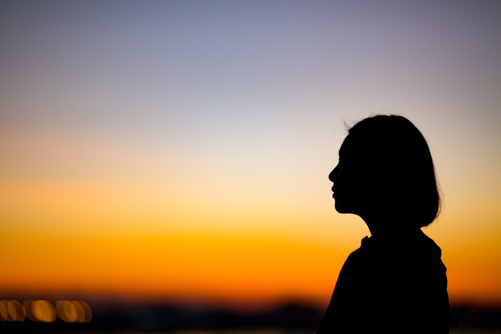 profile of a woman looking out over sunset