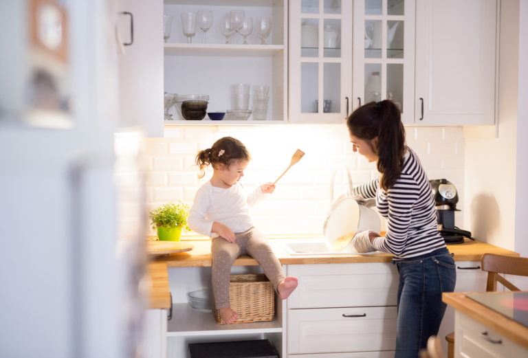 Mother and toddler daughter in the kitchen baking together