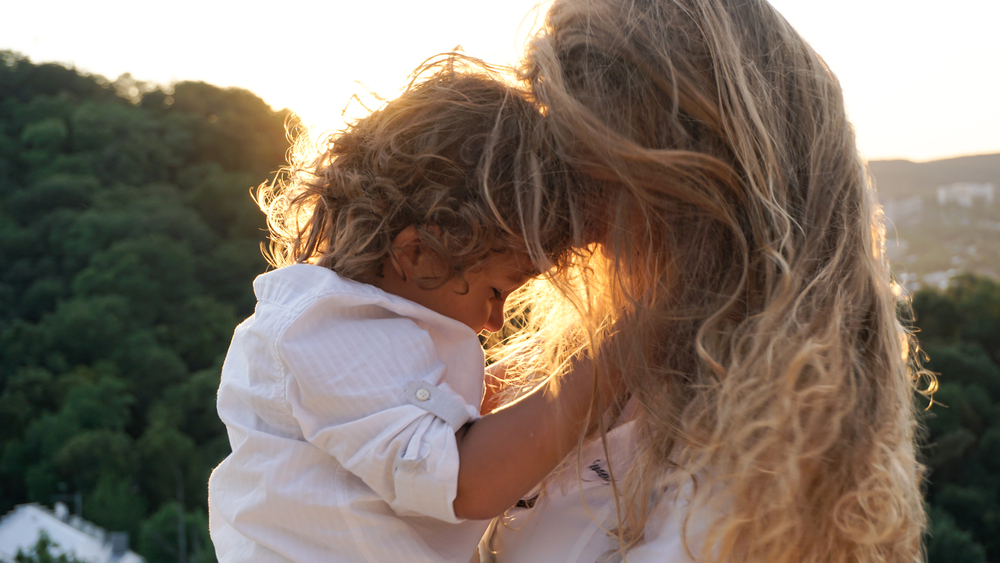 Mother and son touching foreheads in the sunset