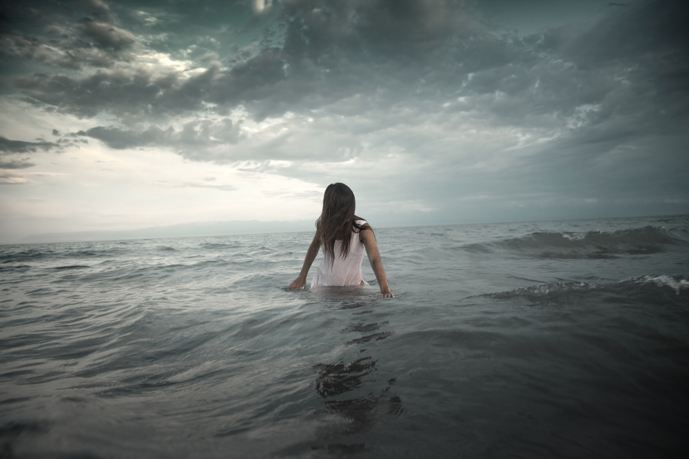 Woman in the middle of water with storm brewing around her