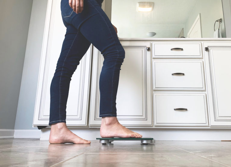 Woman stepping on scale in bathroom checking her weight