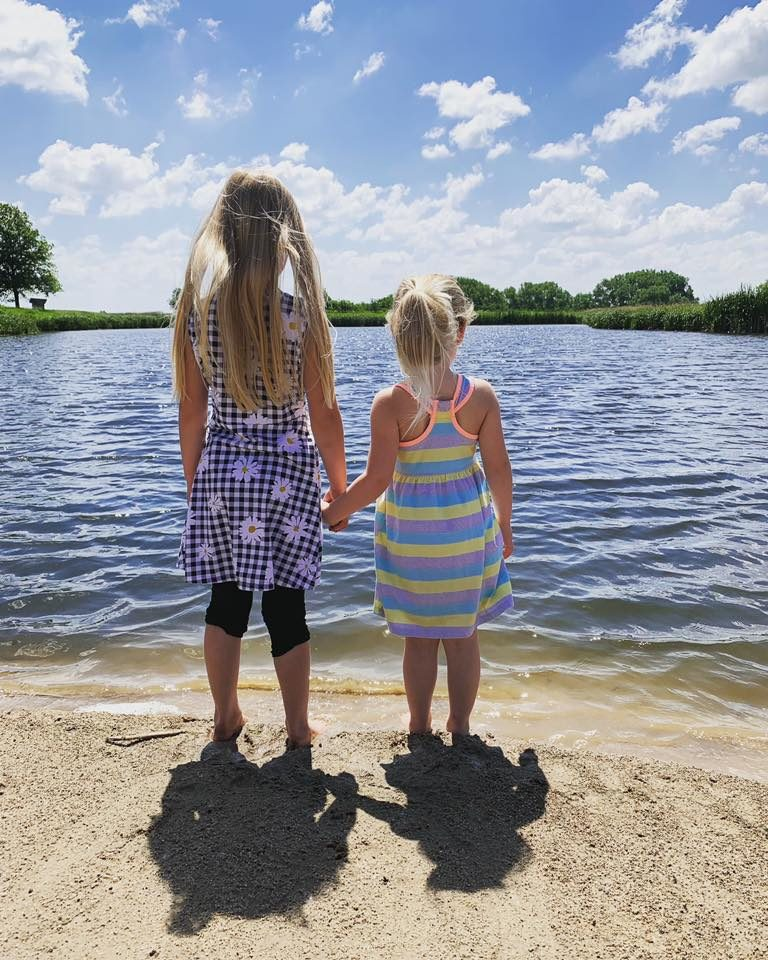 Two little girls standing at the edge of lake