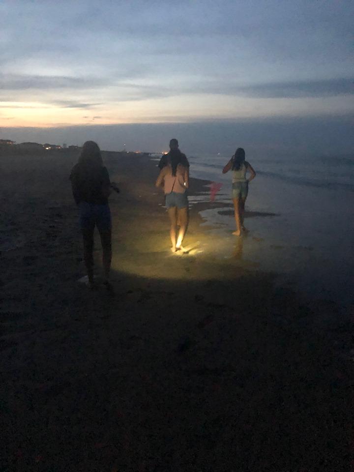 Teens walking on beach at night