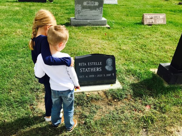 Two kids stand beside their grandma's grave