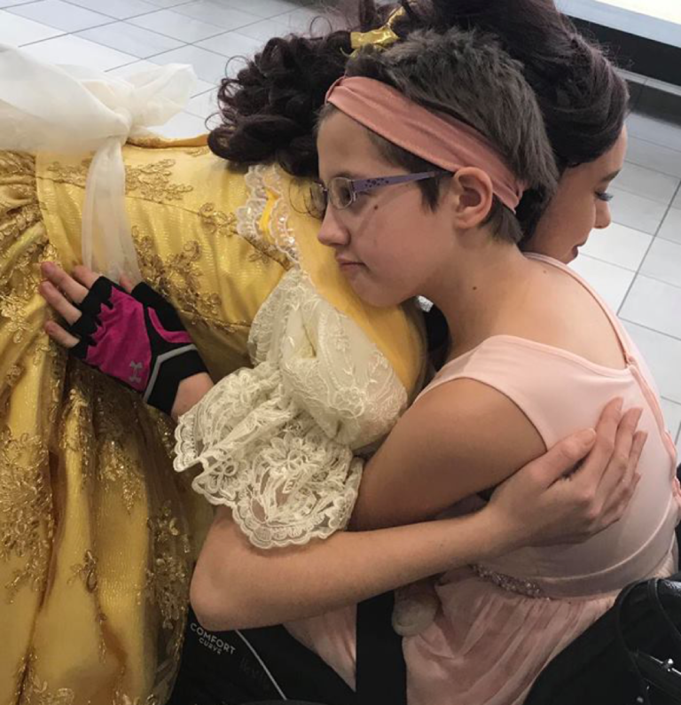 child in wheelchair hugging princess