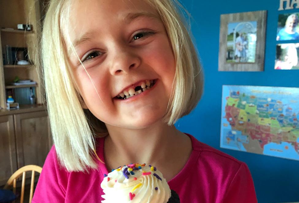 kindergarten child smiling holding a cupcake