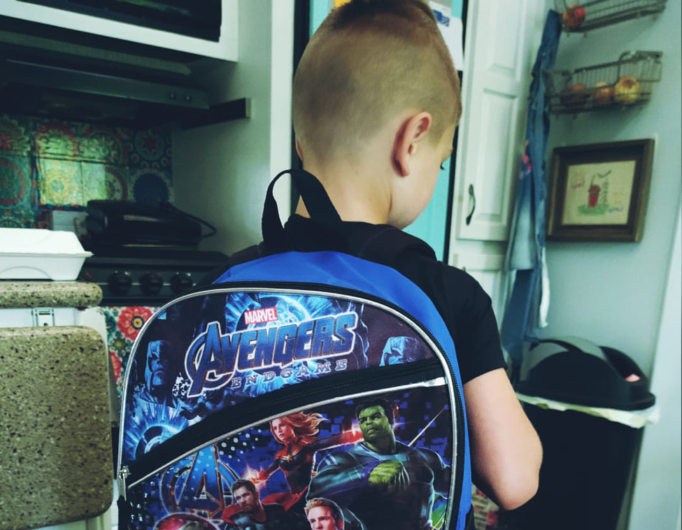 Young boy wearing backpack first day of school