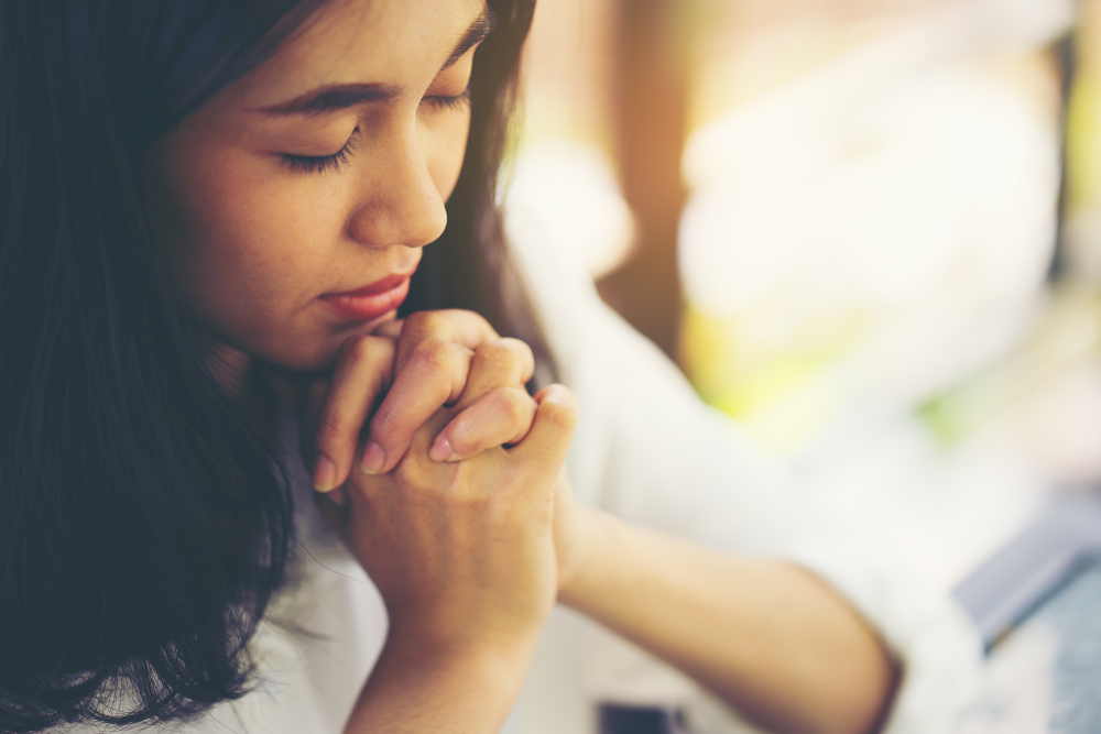 Woman praying with eyes closed