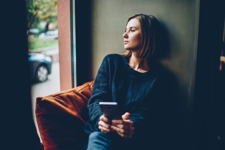 Sad woman holding coffee looking out window